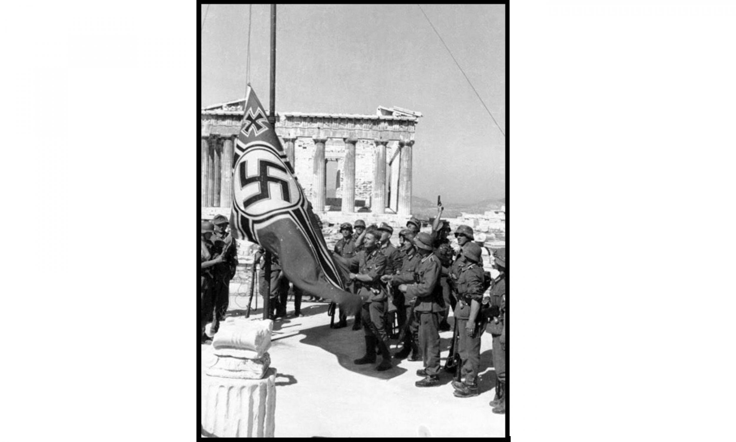 Niemieccy żołnierze wciągający na maszt flagę ze swastyką, w tle Akropol. 1941 rok. Fot. Universal History Archive/UIG via Getty Images