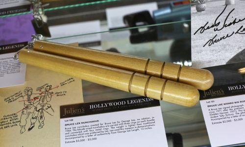 """Nunczako, rodzaj broni obuchowej w formie dwóch pałek połączonych ze sobą za pomocą łańcucha lub linki. Zaistniało w kulturze masowej Zachodu za sprawą filmów sztuk walki. Mistrzowski popis władania tą bronią zaprezentował Bruce Lee właśnie w filmie """"Wejścia smoka"""". Na zdjęciu jego nunczako wystawione na licytację zorganizowaną pod haslem """"Hollywood Legends"""" w Julien's Auctions Gallery 1 kwietnia 2013 roku w Beverly Hills w Kalifornii. Fot. Imeh Akpanudosen / WireImage via Getty Images"""