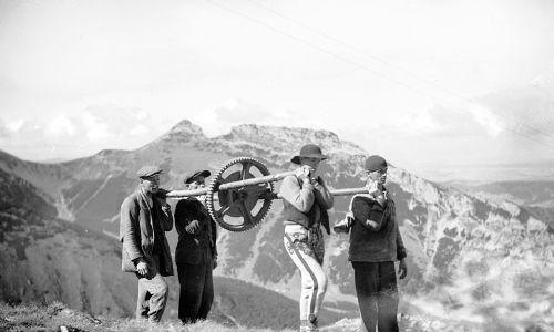 Budowa kolejki linowej na Kasprowy Wierch. Transport części składowych roboczej kolejki linowej - koło zębate wyciągarki. W głębi widok na Giewont od strony południowej. 1935. Fot. NAC/IKC, sygn. 1-G-3820-6