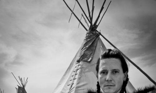 Dariusz Szybka w skórze, w tle tipi jego wioski. Odświętnie ubrani Indianie są głównie podczas ceremonii  i święta muzyki i tańca Pow-wow, które stanowi pomost między tradycją starą, kiedy jeszcze żyli na wolności, a współczesną, kiedy żyją w rezerwatach. Fot. Dariusz Zaród, archiwum prywatne DS