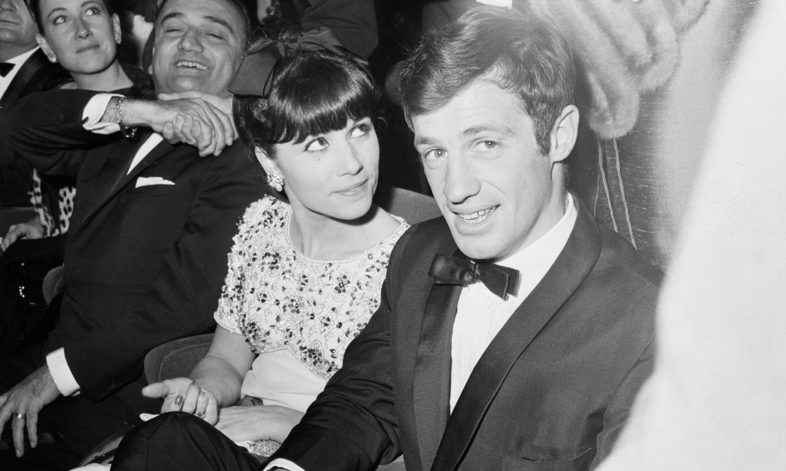 """Podczas wieczornych eskapad z kumplami po knajpach, Jean-Paul poznał niewysoką tancerkę. Zagadał do niej imieniem Elodie. – Mam na imie Renée – odrzekła. Młodziutka para (on 20 lat, ona 19) pobrała się, szybko doczekała się trojga dzieci. Małżeństwo potrwało od 1952 do 1968 r. – ostatnie trzy lata byli w separacji). Belmondo i Renée/Elodie Constantin podczas premiery filmu """"Weekend w Zuydcoote"""" w Paryżu, 1964 r. Fot. KEYSTONE-FRANCE/Gamma-Rapho via  Getty Images"""