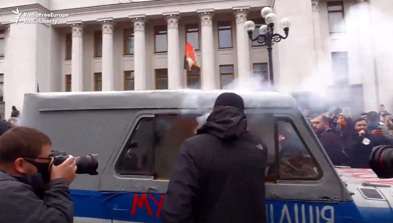 Protestujący wrzucili bomby dymne do starego pojazdu policyjnego przed parlamentem w Kijowie (fot. Radio Free Europe / Radio Liberty)