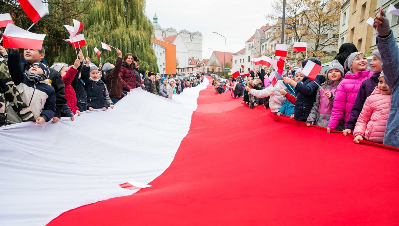 Uczniowie i nauczyciele ze Szkoły Podstawowej nr 63 w Szczecinie idą przez miasto z 200 metrową flagą Polski  (fot. PAP/Jerzy Muszyński)