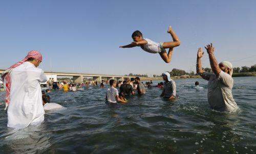 Mieszkańcy zajętego przez ISIS miasta kąpiacy się w Eufracie. Fot. REUTERS/Stringer