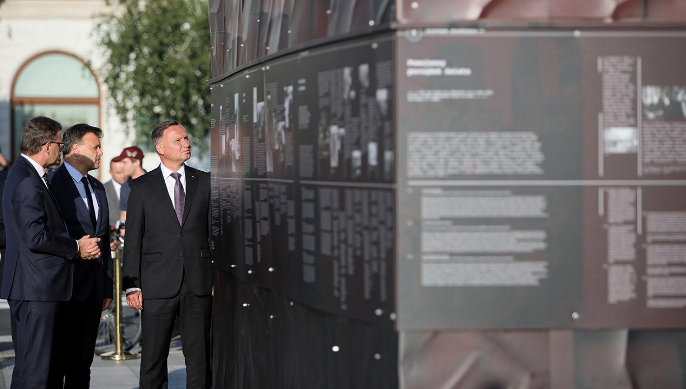 """Prezydent Andrzej Duda (3L) zwiedza wystawę plenerową """"Ściany Totalitaryzmów Polska 1939-1945"""