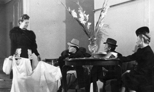 """Zofia Hebda, mimo braku tkanin na rynku, co chwila prezentowała nowe modele strojów i organizowała pokazy mody, na których je prezentowała. W """"Falbance"""" sprzedawano nie tylko ubrania, ale również perfumy, kapelusze czy dodatki. Wykonywano w niej także stroje teatralne i rewiowe. Na zdjęciu ekspedientka pokazuje kupującym suknię ślubną. Fot. NAC/Jerzy Łuczyński, Wydawnictwo Prasowe Kraków-Warszawa, sygnatura: 2-7138"""
