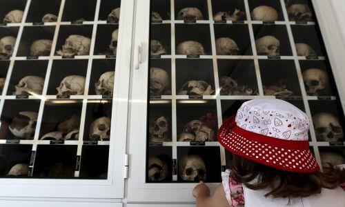 Dziecko wskazuje na czaszkę swojego pradziadka, znajdującą się w mauzoleum niemieckiej masakry w Distomo. 10 czerwca 2015 r. Fot. REUTERS / Yannis Behrakis