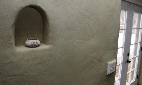 Doktor Mark Lung wyrzeźbił tę wnękę w słomianej ścianie sypialni swego domu w Boise w amerykańskim stanie Idaho, który zbudował dla siebie, swojej żony i ich dwóch psów. Ściany domu są uformowane z bel słomy i pokryte tynkiem wykonanym z gliny, piasku, wapna, słomy i wody. W ocenie Lunga materiały sprawiają, że dom jest wyjątkowo dobrze izolowany. Fot. Joe Jaszewski / Idaho Statesman / MCT via Getty Images