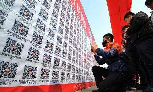"""Chińska """"aplikacja do wszystkiego –  od płatności, przez media społecznościowe po zakupy –  służy też do poszukiwania pracy. Na zdjęciu targi pracy – 2. Shanxi Exhibition Hall Job Fair – w marcu 2015 r. w Taiyuan, stolicy prowincji Shanxi. Nowy tryb rekrutacji """"Offline 2 Online"""" działa za pomocą kodu QR WeChat, który zawiera ofertę i oczekiwania pracodwany, a po jego zeskanowaniu osoby poszukujące pracy zamieszczają CV w tym samym miejscu na WeChat. Fot. Visual China Group via Getty Images"""
